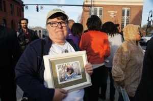 Leslie Boyd holds a picture of Mike, lost at 31 from cancer and denied health care due to a pre-existing condition.