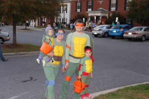 A family dressed as teenage mutant ninja turtles getting ready to trick or treat.