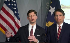 N.C. Governor Pat McCrory listening to State Budget Director Lee Roberts addressing the media at the Joint Force Headquarters Media Briefing Room in Raleigh, N.C. on Thursday, March 5, 2015.  Photo courtesy of Corey Lowenstein