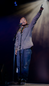 G Yamazawa performs slam poetry on stage. Via GYamazawa.com