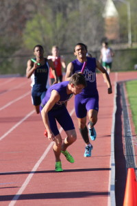 Dylan Andrade handing off the baton to Justin Kenard in the 400 meter relay. Photo by Calvin Inman