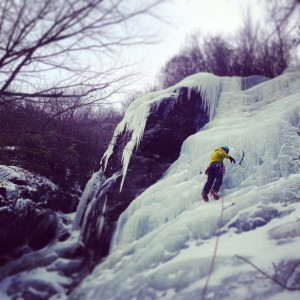 Haas climbing up the face of an ice wall. Photo by