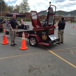 Officer stands by as the next volunteer lines up to get on the Convincer. Photo by David Johnson.