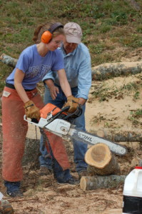 Sophomore Ali Coscore learns how to operate the chainsaw